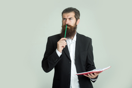 book jacket: young handsome bearded man scientist or professor businessman with long beard in jacket holding book or notepaper and pencil on grey background Stock Photo