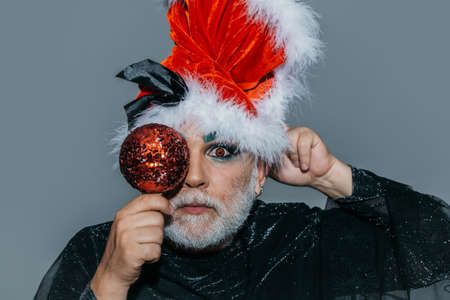 eye ball: New year man with white beard on serious face in santa claus hat and black sparkling cloth holding shiny christmas ball opposite his eye posing on gray background studio Stock Photo