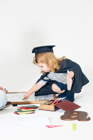 academic gown: Little boy child in black academic gown and squared hat playing with drawing school board holding marker near box with colored pencils isolated on white background