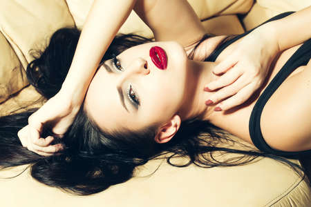 Attractive girl with red lips on the beige couch. Relaxed sexy girl with red lips on the sofa