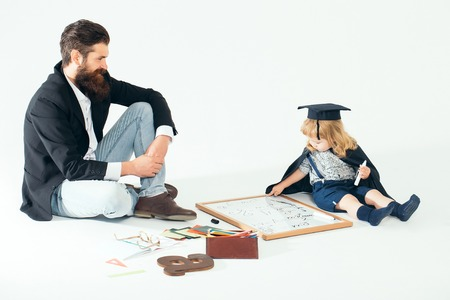 academic gown: Small boy child in black academic gown and squared hat and bearded professor man in glasses drawing by marker on blackboard near school supplies on white background isolated