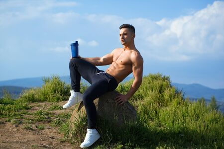 sexi: Young sexy man with muscular sexy body and bare torso with chest sitting outdoor with water bottle on sky natural background