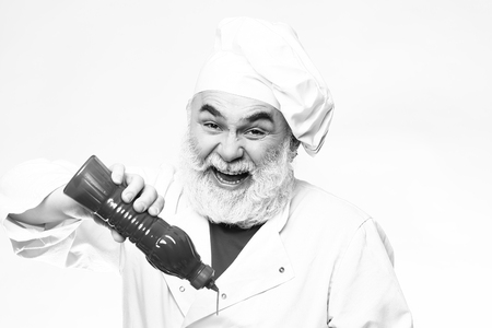Bearded chef with ketchup bottle and smiling face in white uniform and hat, black and white