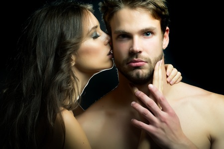 sexual foreplay: Closeup portrait of young beautiful sexual couple of brunette woman with long hair embracing and kissing handsome muscular man in studio on black background, horizontal picture Stock Photo
