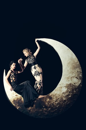crescent: Beautiful young women with blonde and brunette hair and red lips posing on crescent moon in long evening elegant dress with lace on black background