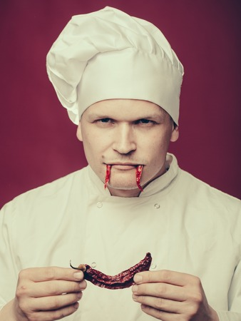 fangs: chef with a red chili pepper in his hands on face as fangs in white uniform and hat on purple background Stock Photo