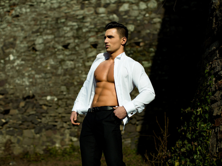 barechested: Man half face bare-chested young handsome sensual model in white shirt gaped open poses with hand in black trousers pocket outside on masonry background Stock Photo