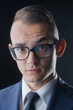 eyebrow raised: young fashion businessman with nerd glasses raised eyebrow and stylish hairdo in jacket with tie on studio background