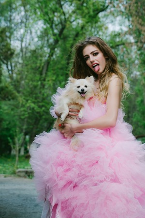 outdoor glamour: Young woman with beautiful face and long curly hair in glamour pink dress showing tongue holding cute small dog outdoor with green trees Stock Photo
