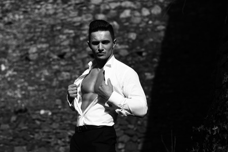barechested: Man bare-chested young handsome sensual model wears shirt trousers looks forward outside black and white on masonry background