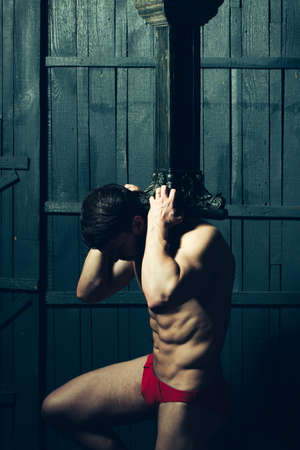 atlantes: Young man with muscular sexy body holding hard column sitting on knee.