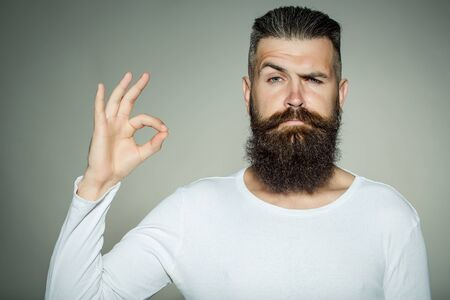 okey: handsome young man with long beard and moustache on face with okey gesture of finger on grey background in studio