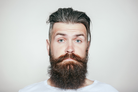 raised eyebrow: handsome young man with long beard and moustache on serious face with raised eyebrow on grey background in studio
