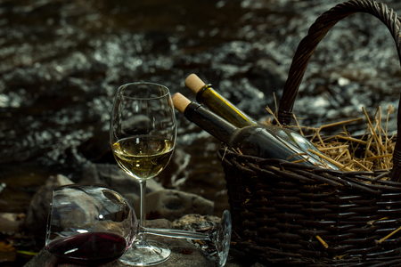 bocal: Wine glass and bottles in picnic basket with straw near water in twilight. Vintage look