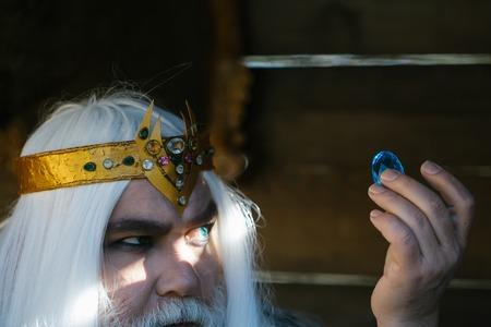 긴 흰 머리카락과 나무 배경에 파란색 보석 돌을 들고 수염 황금 왕관에 오래 된 수염을 가진 남자 마법사
