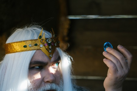 Old bearded man wizard in golden crown with long white hair and beard holding blue gem stone on wooden background Imagens - 61863097