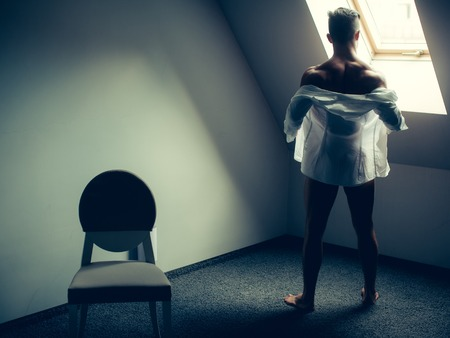 undressing: Muscular man undressing with white shirt standing near chair and looking out the window