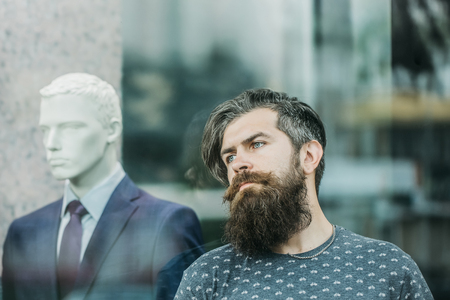 hairy closeup: handsome bearded young man hipster with long beard and mustache has stylish hair on serious hairy face standing near shop glass showcase with dummy in suit, closeup Stock Photo
