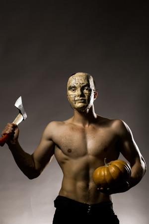 nackte brust: Junger stattlicher Mann in der Maske der Zeitung mit muskulösen Körper nackte Brust und Oberkörper posiert im Studio gelb Halloween-Kürbis und Axt auf grauem Hintergrund