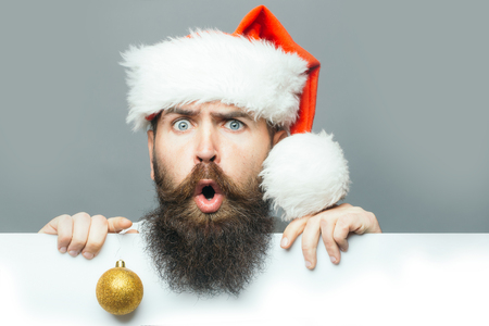 handsome bearded man with long lush beard and moustache on surprised face decoration ball in christmas hat with paper sheet on grey background
