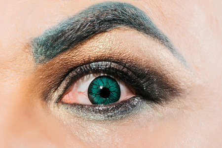 eyebrow  look: Male eye with decorative colored green contact lens dark eyeshadow makeup and hairy eyebrow with amazed look closeup Stock Photo