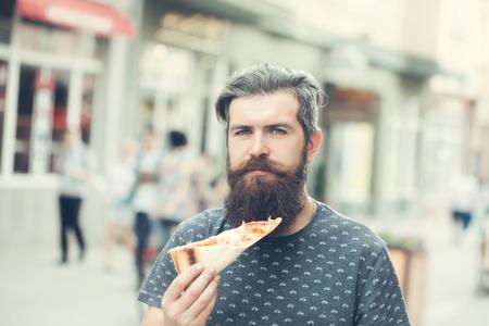 knappe sexy bebaarde jongeman hipster met een lange baard en snor op ernstige harige gezicht van het eten van pizza op straat buiten