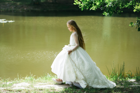 prom queen: small girl kid with long blonde hair and pretty smiling happy face in prom princess white dress standing sunny day outdoor near water