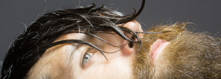 hairy closeup: handsome bearded young man hipster with long beard and mustache has wet hair on serious hairy face, closeup Stock Photo