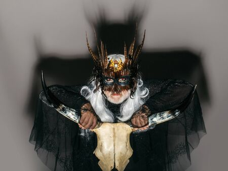 cranium: Gothic man in masquerade mask with feathers on his face long white hair and beard in black theater costume on background of big shadow holding cranium of horned animal Stock Photo