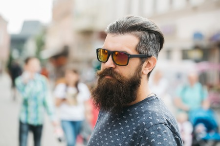 hairy closeup: handsome bearded young man hipster with long beard and mustache has stylish hair on serious hairy face in sun glasses outdoor, closeup Stock Photo