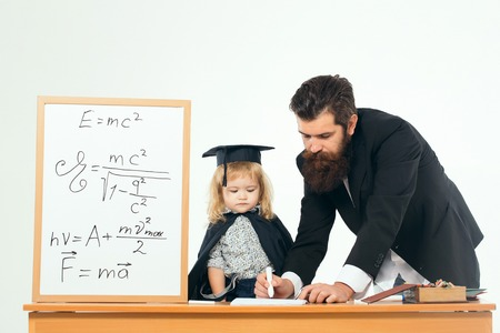 academic gown: Man professor with beard writing by marker on paper with cute boy student small child in black academic gown and squared hat at desk near school board with formulas on white background isolated