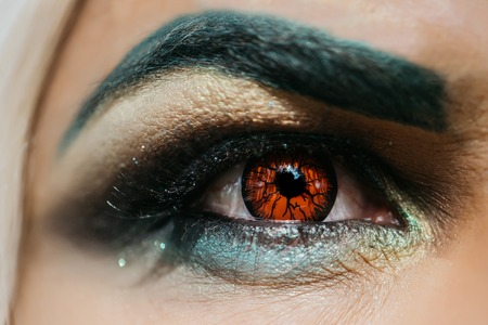 eyebrow  look: Male eye with dark eyeshadow makeup black eyebrow and orange colored decorative contact lens with serious look closeup