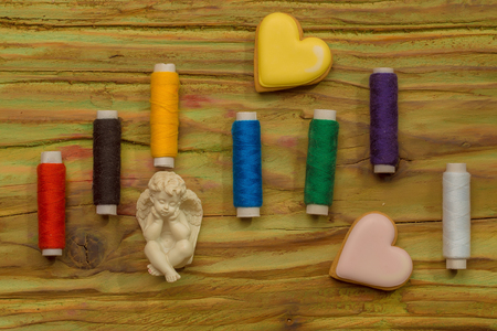 trabajo manual: Set of bobbins of sewing colorful stitch for handwork cookies in heart shape and figure of angel on wooden background Foto de archivo