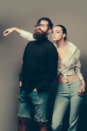 studio model: young sexy couple of woman with pretty face in stylish white shirt bra and pants near handsome bearded man with long beard in jeans shorts in studio on grey background