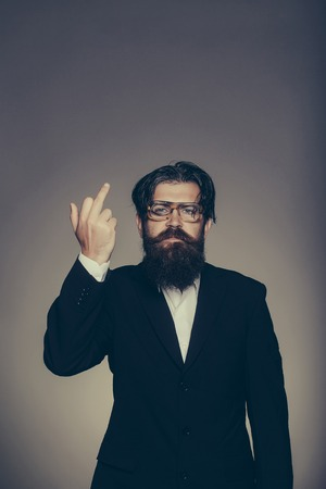 gives: Rude man bearded hipster male in vintage glasses suit gives middle finger on grey wall