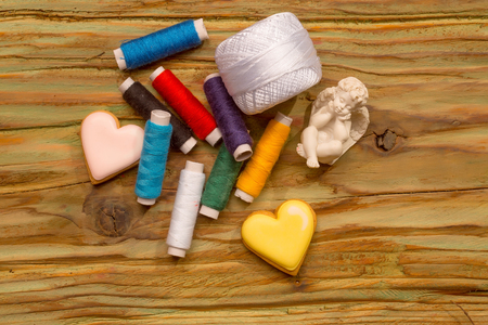 Bobbins of colorful cotton sewing stitch figure of angel hank of yarn and homemade cookies in shape of heart on wooden background