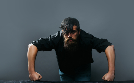 pushes: Attractive guy pushes hands into the table. Handsome man with the beard and wet hair
