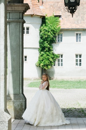 prom queen: small girl kid with long blonde hair and pretty smiling happy face in prom princess white dress standing sunny day outdoor near building Stock Photo