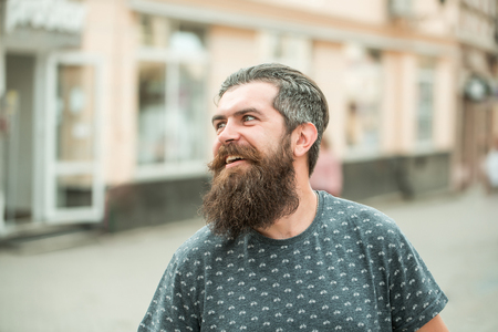 hairy closeup: handsome sexy bearded young man hipster with long beard and mustache has stylish hair on smiling hairy face outdoor, closeup Stock Photo