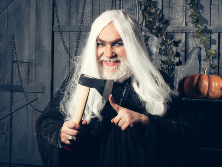 house robes: Old grey-haired sorcerer in black robe with demonic smile hold axe near finger in wooden house