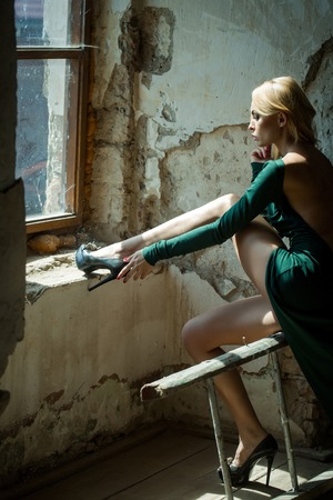 splendid: Young woman blonde with splendid legs dressed in sexy green dress with bare back and high-heeled black shoes posing in old room at window indoor