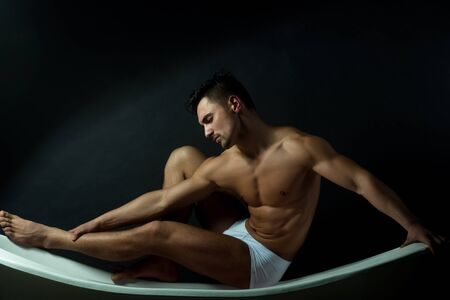 nackte brust: Handsome young man in white panties with sexy bare muscular torso sitting on bathtub