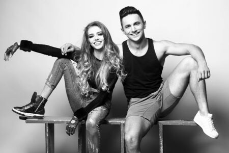 Beauty and fashion, friends. Young couple sitting in studio, black and white