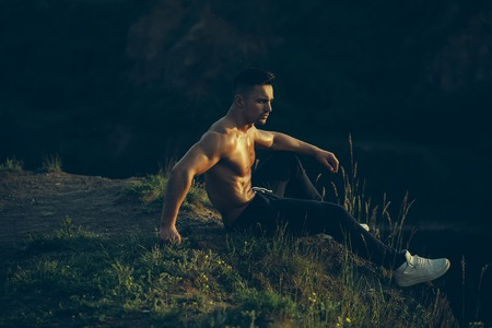 sexi: young macho man model athlete with muscular sexy body and wet bare chest outdoor on hill with city landscape