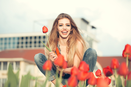 ragazza innamorata: happy beautiful young slender girl is sitting with red tulips