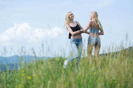 sexi: young pretty women with long lush curly blonde hair and sexy bodies standing in green field with grass and blue cloudy sky outdoor on natural background Stock Photo