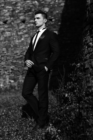 trouser legs: Man half face young handsome elegant model in suit with skinny necktie poses with hand in trouser pocket one leg backward outdoor black and white on masonry background