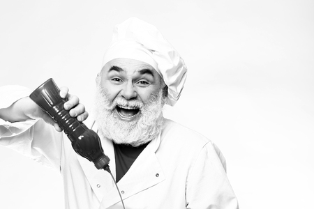 ketchup bottle: Bearded chef with ketchup bottle and smiling face in white uniform and hat, black and white