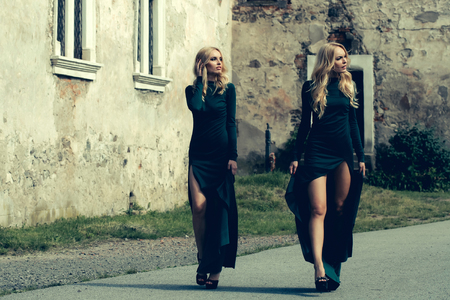sisters sexy: young pretty women with long lush curly blonde hair and sexy bodies in green dresses walking near stony building with windows outdoor Stock Photo