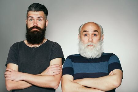raised eyebrow: Old and young bearded men with long beard white and brown and raised eyebrow on surprised faces in studio on grey background